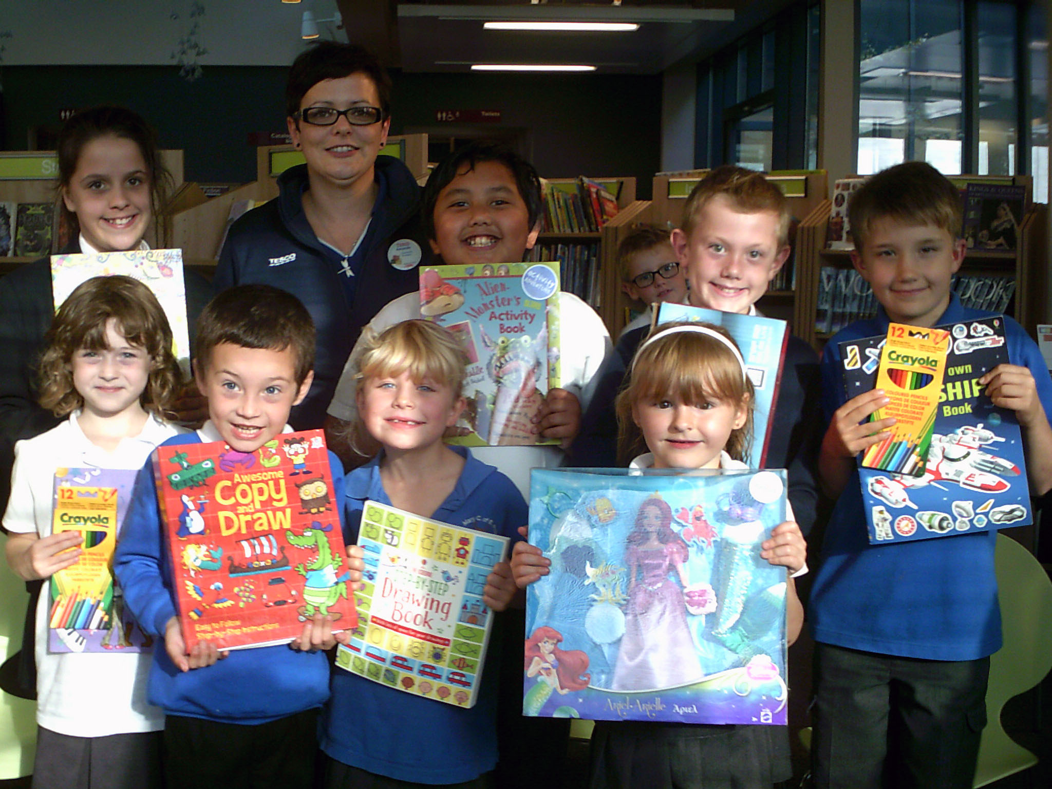 Some of the winners of the colouring competition: The back row from the left - Alexandra Archer (1st prize older category), Community Champion for Tesco Paignton Metro Amanda Nelhams, James Carlo Mund
